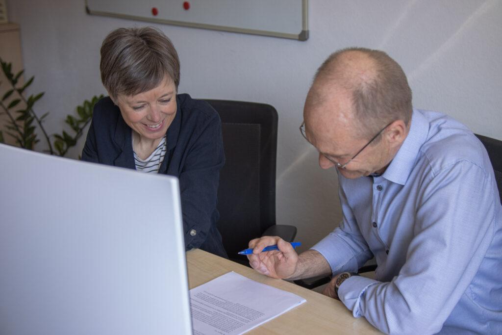 Zwei Kollegen arbeiten gemeinsam an einem Projekt.